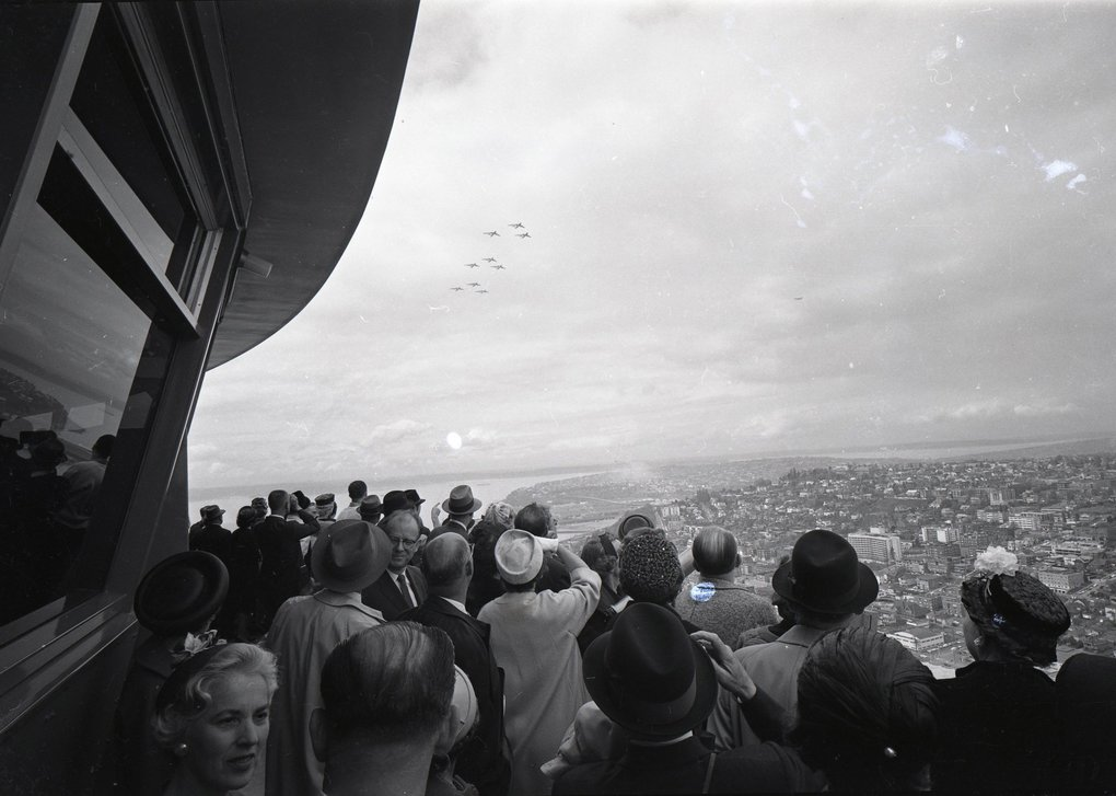 Spectators watch from the Space Needle as planes fly in formation toward Seattle Center on April 21, 1962.  (Vic Condiotty / The Seattle Times)