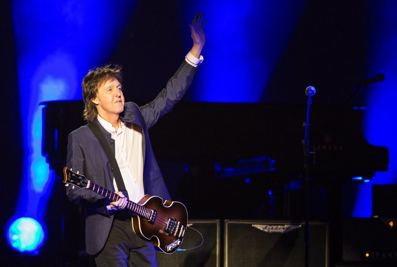 "Sir Paul McCartney waves at a cheering crowd as he takes the stage for his ""One on One"" tour at KeyArena on Sunday, April 17, 2016. (Lindsey Wasson/The Seattle Times)"