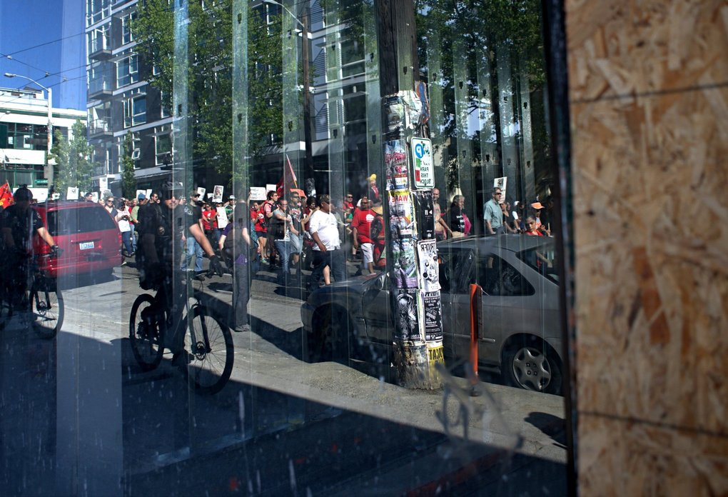 The march passes by boarded up windows on businesses near Melrose Ave and  E. Pine st. on Capitol Hill the annual worker's march sponsored by El Comité and the May 1st Action Coalition on Sunday. (Lindsey Wasson / The Seattle Times)