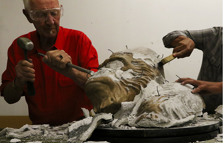 At the reveal, sculptor Douglas Granum CQ removes the ceramic shell surrounding the bronze head of Ivan the Gorilla, being cast in multiple parts with Ivan's ashes in the bronze at 2 Ravens Studio in Tacoma.