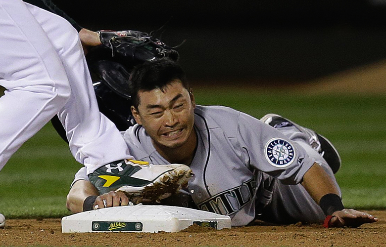 Seattle Mariners' Norichika Aoki, right, slides safe with a steal of third base beneath Oakland Athletics' Mark Canha in the seventh inning of a baseball game Monday, May 2, 2016, in Oakland, Calif. (AP Photo/Ben Margot)