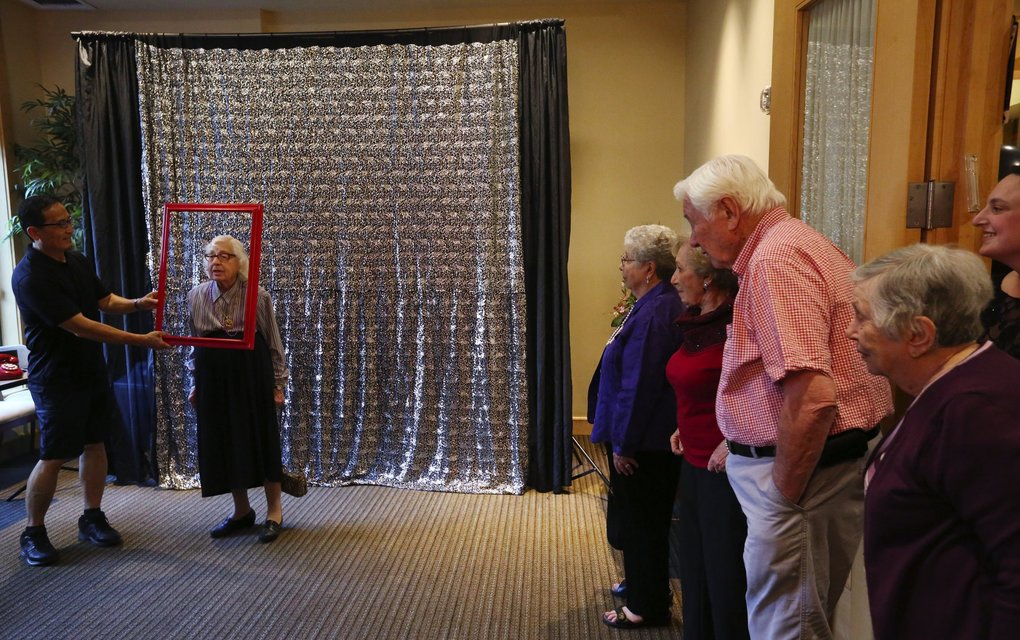 "Residents at the Summit At First Hill retirement home, wait their turn at the photo booth at their ""senior senior prom"" event. (Ken Lambert / The Seattle Times)"