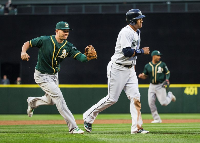 Leonys Martin limps as he is tagged out along the third basepath by Oakland's Danny Valencia in a May 25 game at Safeco Field. Martin has been on the DL with a hamstring injury. (Dean Rutz/The Seattle Times)