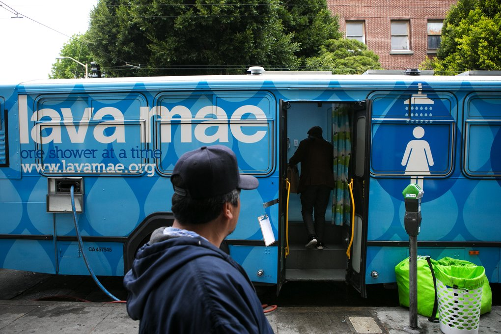 Showers and toilets for the homeless are available at a Lava Mae bus parked outside the Mission Neighborhood Resource Center on May 14. Lava Mae is a San Francisco company that repurposes old transportation buses into showers and toilets for mobile hygiene for the homeless. The buses are parked around the city on a set schedule.  (Bettina Hansen/The Seattle Times)