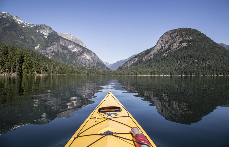 Kayaking on Ross Lake between the shadows of an unidentified peak at left and Pumpkin Mountain at right. (Steve Ringman / The Seattle Times)