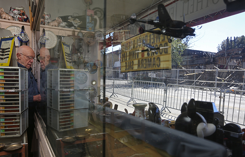 In the wake of Friday's devastating fire in Bothell, damage seen at right, Rachman Cantrell sets up his window display after opening his store, Bothell Jewelers & Collectibles, which he has operated for 29 years, Sunday, July 24, 2016.