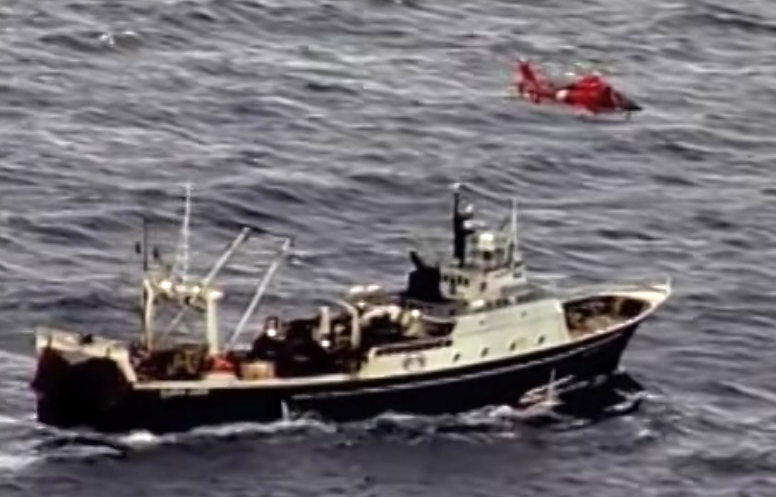 In this frame from a 2013 video from the U.S. Coast Guard, a helicopter lifts an injured man from the deck of the Alaskan Juris June 21, 2013.
