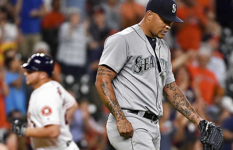 Seattle Mariners starting pitcher Taijuan Walker, right, looks away as Houston Astros' A.J. Reed, left, rounds the bases after hitting a two-run home run in the fourth inning of a baseball game, Tuesday, July 5, 2016, in Houston. (AP Photo/Eric Christian Smith) TXES114