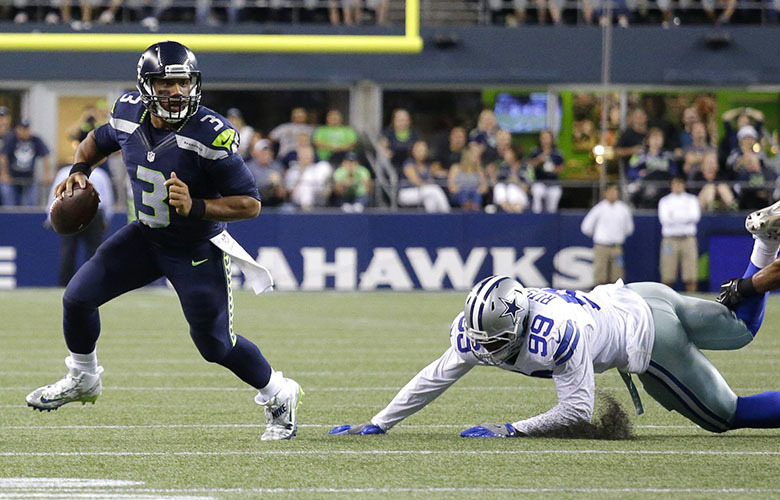 Seattle Seahawks quarterback Russell Wilson (3) scrambles away from Dallas Cowboys defensive end Ryan Russell (99) before throwing a touchdown pass to Tyler Lockett, not seen, duirng the second half of a preseason NFL football game, Thursday, Aug.