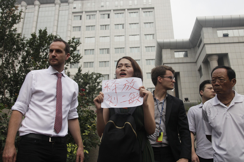 """In this Monday, Aug. 1, 2016 photo, Li Wenzu, center, wife of imprisoned lawyer Wang Quanzhang, holds a paper that reads """"Release Liu Ermin"""" stage a protest next to members of foreign diplomats and supporters of a prominent Chinese human rights lawyer and activists outside the Tianjin No. 2 Intermediate People's Court in northern China's Tianjin Municipality. In halting televised confessions and emotional courtroom testimony, Chinese lawyers and activists held in a government crackdown have intoned the same ominous refrain: Shadowy foreign forces are funding, directing and encouraging activities bent on destabilizing China's government and smearing its reputation. (AP Photo/Gerry Shih)"""