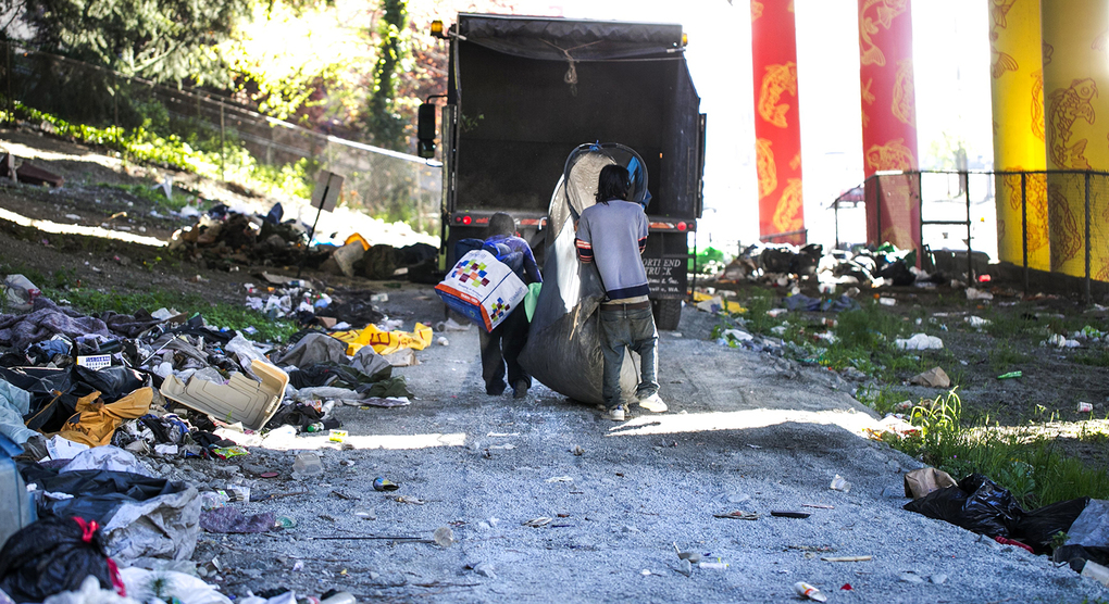 Homeless campers relocate their belongings across South Jackson Street as maintenance workers from the state Department of Transportation clear encampments under Interstate 5 in Seattle. (Bettina Hansen/The Seattle Times)