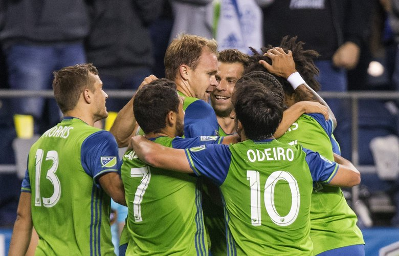 The Sounders gather around Chad Marshall, whose goal at 23:14 of the first half of play giving Seattle a 1-0 lead over the Chicago Fire. (Dean Rutz / The Seattle Times)
