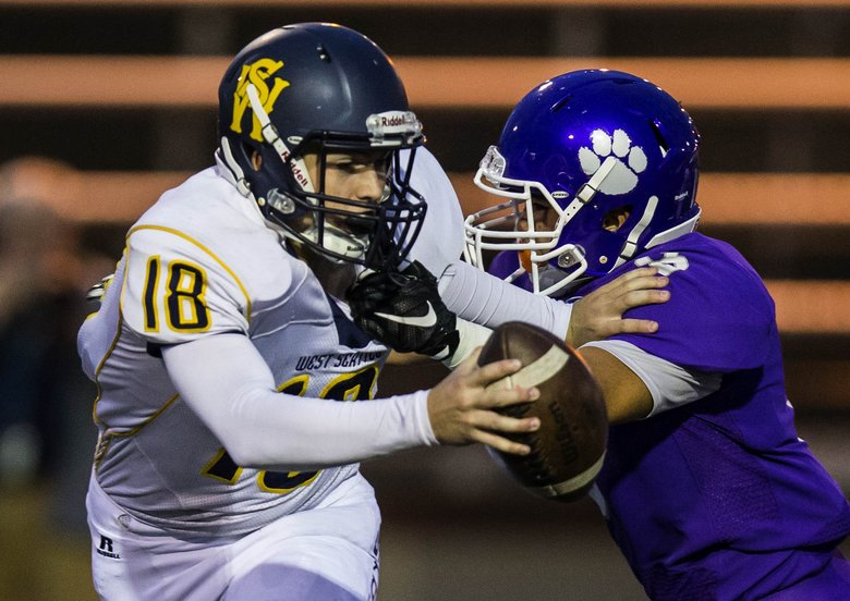West Seattle quarterback Gabe Gangon takes an 11-yard sack at the hands of Garfield's Jason Nguyen in the first quarter Friday.  (Dean Rutz / The Seattle Times)