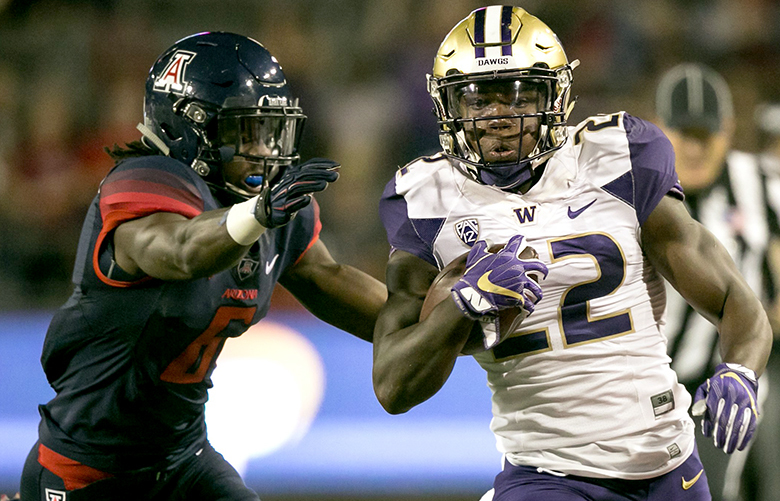 Washington Huskies running back Lavon Coleman (22) runs for a 38 yard gain as Arizona Wildcats safety Demetrius Flannigan-Fowles makes the tackle to prevent a touchdown in the second quarter.