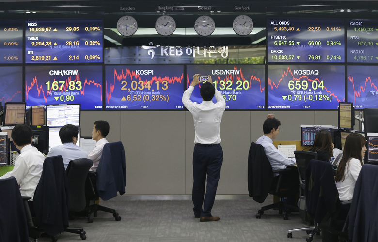 A currency trader uses a smartphone to take pictures of screens showing Korea Composite Stock Price Index (KOSPI), center left, and foreign exchange rate, center right, at the foreign exchange dealing room of the KEB Hana Bank headquarters in Seoul, South Korea, Tuesday, Oct. 18, 2016. Asian stock markets rose Tuesday ahead of China's release of quarterly growth data and a policy meeting of the European Central Bank later in the week. (AP Photo/Ahn Young-joon)