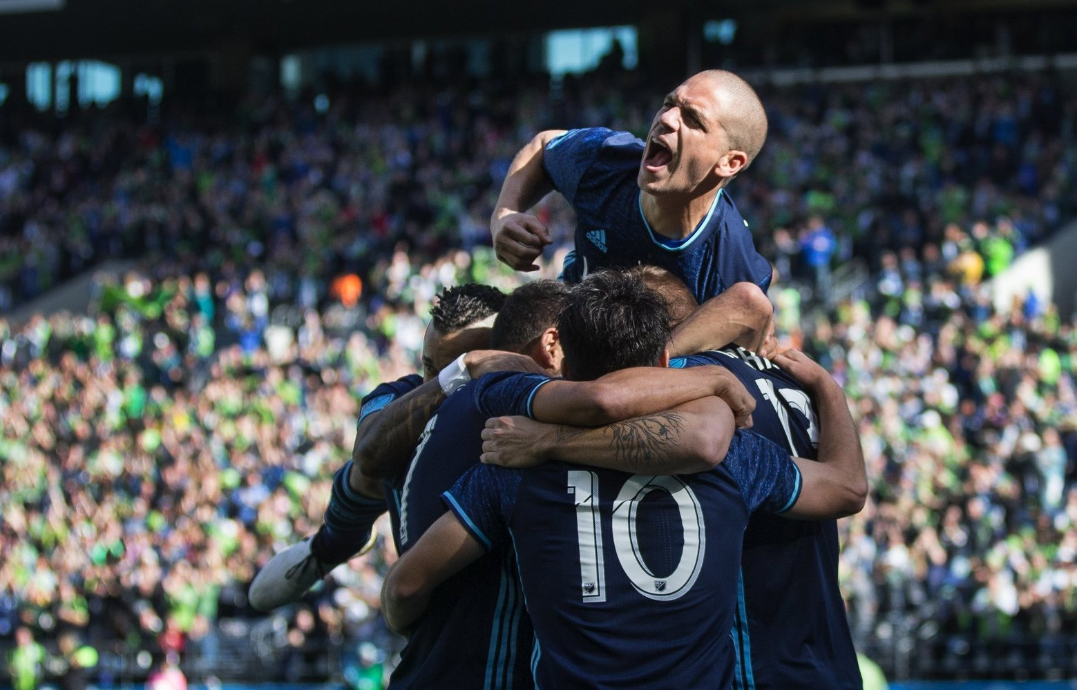Seattle Sounders midfielder Osvaldo Alonso jumps onto a circle of his teammates as they celebrate striking first on a goal from midfielder Alvaro Fernandez in the first half. (Lindsey Wasson / The Seattle Times)