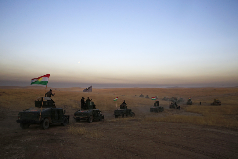 FILE – In this Monday, Oct. 17, 2016 file photo, a Peshmerga convoy drives towards a frontline in Khazer, about 30 kilometers (19 miles) east of Mosul, Iraq. Simultaneous attacks on the Islamic State-held city of Mosul in Iraq and Raqqa, the de facto IS capital across the border in eastern Syria, would make military sense: They would make it harder for the extremists to move reinforcements and deny them a safe haven. (AP Photo/Bram Janssen, File)