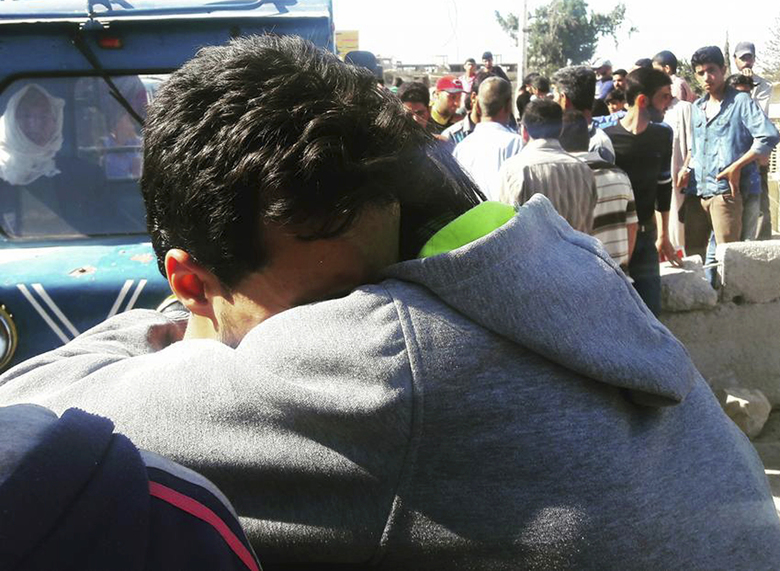 Two Syrian men hug each other as they prepare to leave the government-besieged Damascus suburb of Moadamiyeh, Syria, Wednesday, Oct. 18, 2016. A Syrian negotiator says 38 buses carrying nearly 2,000 people, including 700 gunmen, have been evacuated from a government-besieged Damascus suburb following a deal to empty it of rebels. (AP Photo)
