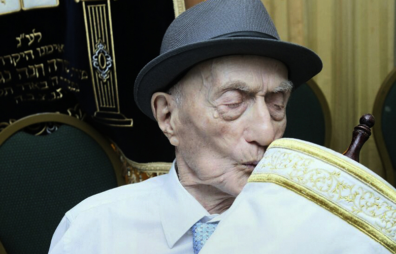This undated photo provided by Kristal family shows Israel Kristal, 113, the world's oldest man, holding a Torah. Kristal lived through both World Wars and survived the Auschwitz concentration camp. Earlier this year, Guinness World Records awarded him a certificate as the world's oldest man. (Kristal family via AP)