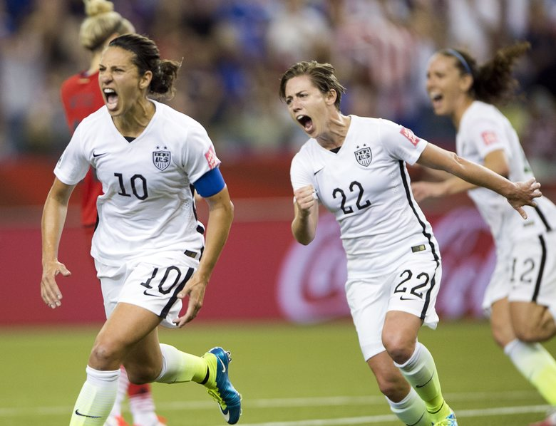 United States' Carli Lloyd reacts after scoring on a penalty kick against Germany as Meghan Klingenberg follows during the Women's World Cup in Montreal in 2015. Lloyd was one of five players to file a complaint with the U.S. Equal Employment Opportunity Commission, alleging that their team had been paid significantly less than their male counterparts. (Ryan Remiorz/AP)