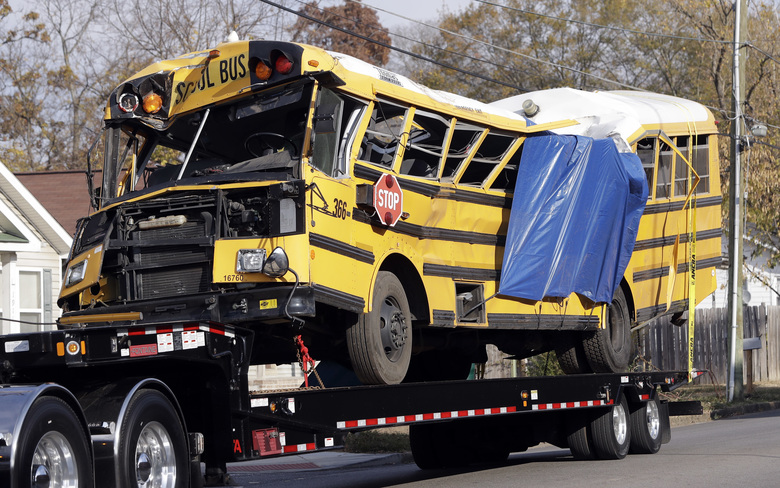 FILE – In a Tuesday, Nov. 22, 2016 file photo, a school bus is carried away, in Chattanooga, Tenn, from the site where it crashed on Monday. Attorney Amanda Dunn says she anticipates bus driver Johnthony Walker will plead not guilty if a grand jury indicts him. He's charged with five counts of vehicular homicide. Police say another count will be added. (AP Photo/Mark Humphrey, File)