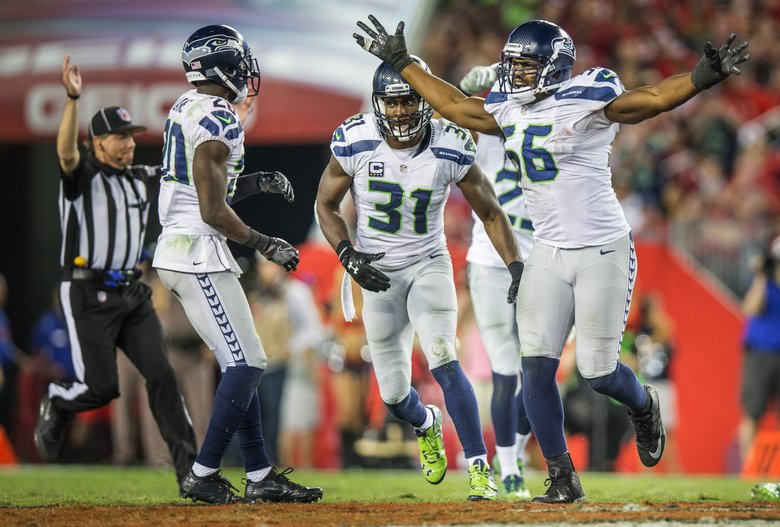 Seahawks Cliff Avri (56), Kam Chancellor (31) and Jeremy Lane celebrate recovering a Tampa fumble in the fourth quarter. (Dean Rutz / The Seattle Times)