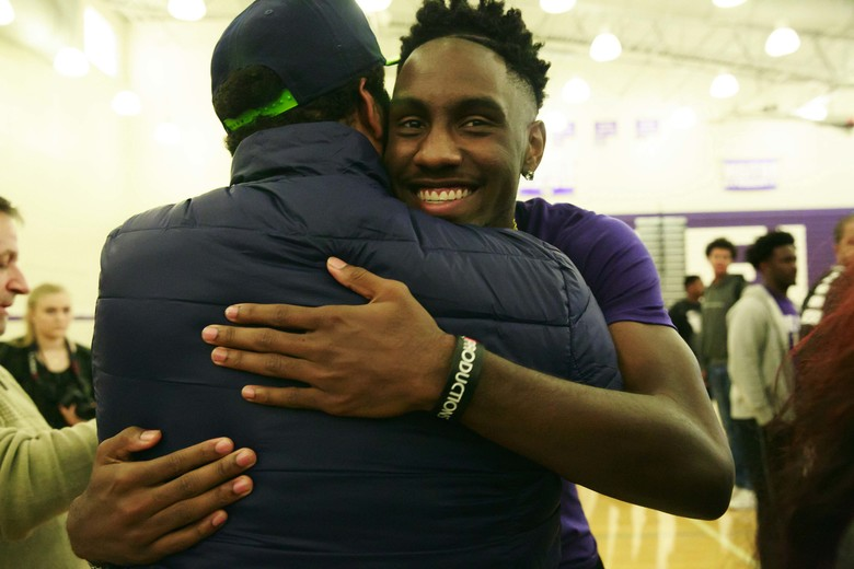 Jaylen Nowell receives a hug during a signing ceremony at Garfield High School in Seattle Wednesday, Nov. 9, 2016. Nowell committed to playing basketball at the University of Washington.  (Erika Schultz/The Seattle Times)