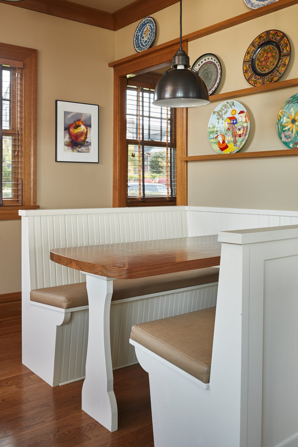 """Miller added display shelves for Kim's """"extensive plate collection,"""" and this built-in breakfast booth near the hallway and service stairs is wired with power and an internet connection so she and Rob """"can take care of morning business.""""  (Benjamin Benschneider/The Seattle Times)"""