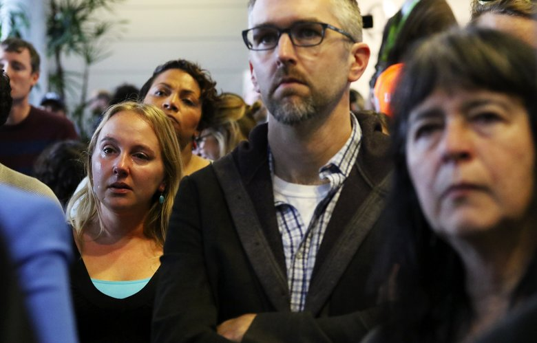 A tear runs down the cheek of Stephanie Celt, left, as she listens to a speaker encouraging everyone to continue their fight during an emotional post-election rally at City Hall Wednesday. (Alan Berner/The Seattle Times)