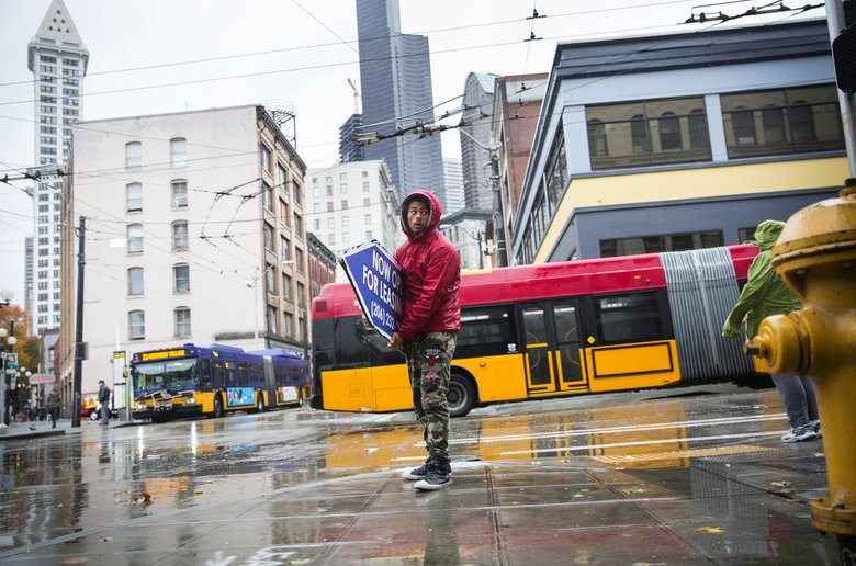 Jeremiah Zueger checks to see if he's got enough space to perform another sign-spinning trick in downtown Seattle. Zueger works for Aarow Sign Spinners, taking the ferry from Bremerton, rain or shine. (Lindsey Wasson/The Seattle Times)