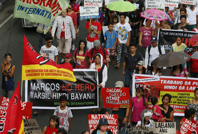 Hundreds of protesters march towards the Presidential Palace to protest the Nov. 18, 2016 burial of the late Philippine dictator Ferdinand Marcos at the Heroes' Cemetery in a secrecy-shrouded ceremony Wednesday, Nov. 30, 2016 in Manila, Philippines. Protests are mounting since the hasty burial of the long-dead Marcos in a heroes' cemetery, in a growing political storm that's lashing the president who allowed the entombment. (AP Photo/Bullit Marquez)