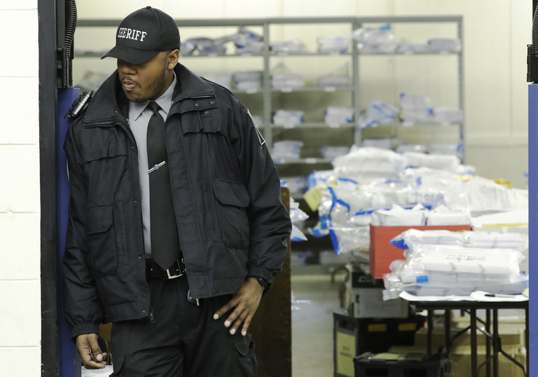 A Milwaukee County sheriff guards a room where ballots are stacked up as a statewide presidential election recount begins Thursday, Dec. 1, 2016, in Milwaukee. The first candidate-driven statewide recount of a presidential election in 16 years began Thursday in Wisconsin, a state that Donald Trump won by less than a percentage point over Hillary Clinton after polls long predicted a Clinton victory. (AP Photo/Morry Gash)