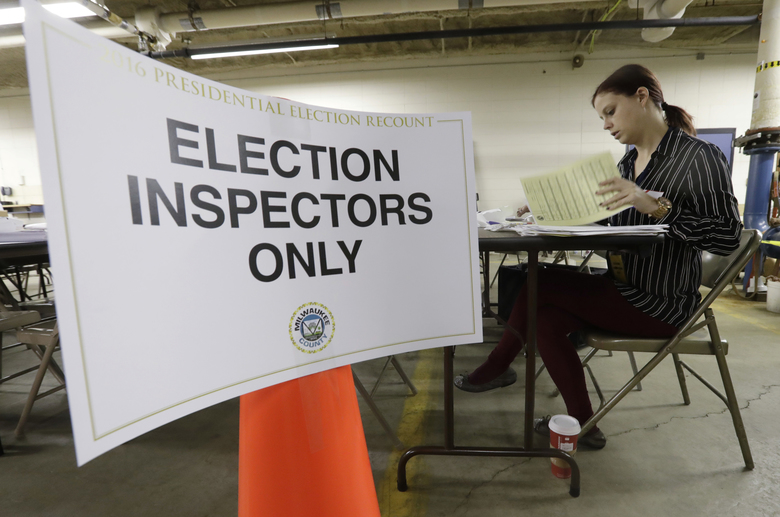Nicole Kirby looks over results during a statewide presidential election recount Thursday, Dec. 1, 2016, in Milwaukee. The first candidate-driven statewide recount of a presidential election in 16 years began Thursday in Wisconsin, a state that Donald Trump won by less than a percentage point over Hillary Clinton after polls long predicted a Clinton victory. (AP Photo/Morry Gash)