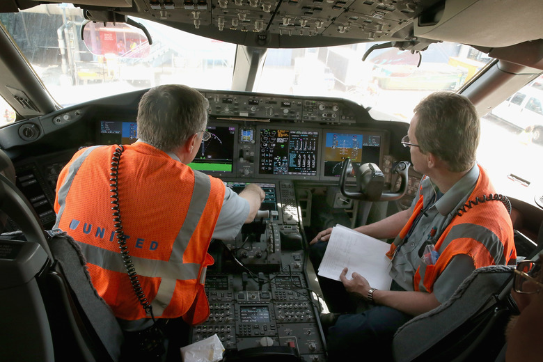 Workers check out the cockpit of a United Airlines Boeing 787 Dreamliner after it arrived at O'Hare International Airport in 2013. (Scott Olson/Getty Images)