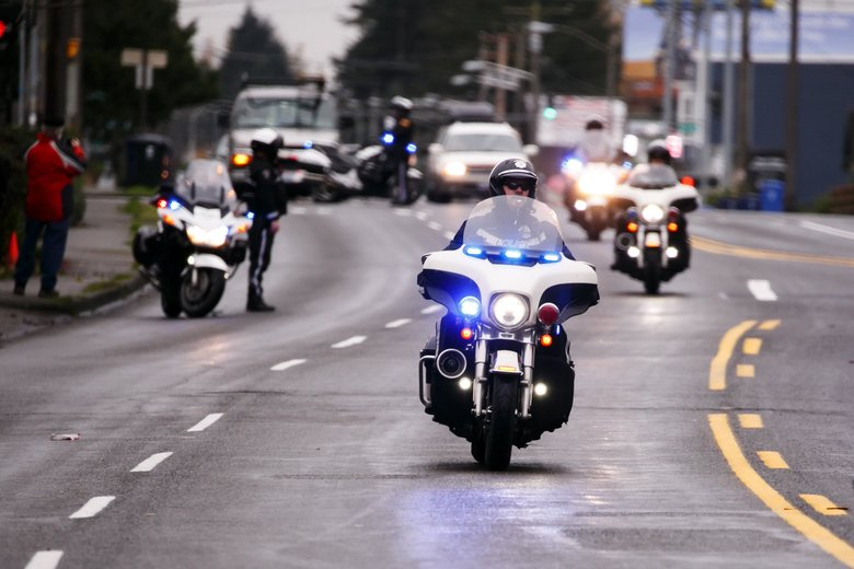 "Officers and emergency personnel travel in a procession for Tacoma police Officer Reginald ""Jake"" Gutierrez in Tacoma, Wash. Friday, Dec. 2, 2016. Crowds gathered to pay respects to Gutierrez near Tuell-McKee Funeral Home, 2215 Sixth Ave., in Tacoma. Tacoma Fire Department displayed flags at the start and end of the procession with aerial ladder trucks.  (Erika Schultz / The Seattle Times)"