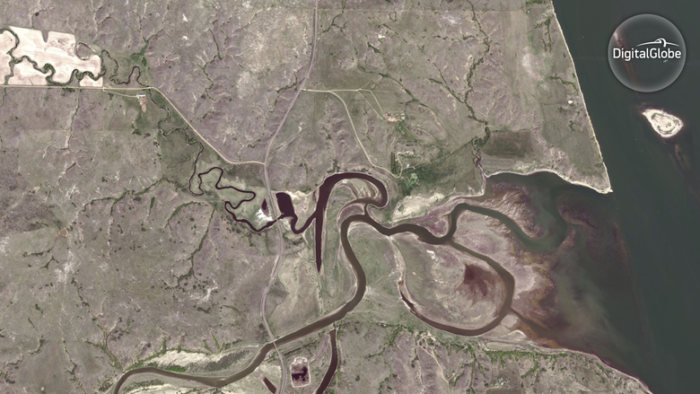In this May 17, 2016 satellite image taken by DigitalGlobe, areas near Cannon Ball, N.D., along Mississippi River, right, are shown before construction began on the Dakota Access pipeline and the start of protests began. (DigitalGlobe via AP)