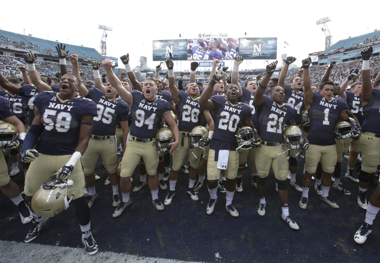 FILE – In this Nov. 5, 2016, file photo, Navy players celebrate after defeating Notre Dame 28-27 in an NCAA college football game Saturday, Nov. 5, 2016, in Jacksonville, Fla. If Navy is in position to earn a spot in a major bowl game when the rankings and semifinal pairings are set Sunday, the 12-person committee will wait a week for Navy to play Army to make a final call on where the Midshipmen should be ranked. (AP Photo/John Raoux, File)