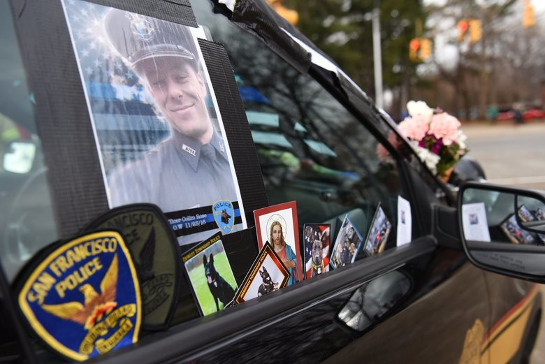 Fallen Wayne State University K-9 Police officer Collin Rose's police SUV is covered with flowers and mementos outside of Rose's funeral at St. Joan of Arc Catholic Church in St. Clair Shores, Mich., Thursday, Dec. 1, 2016. Rose was shot Nov. 22 as he tried to arrest DeAngelo Davis, who faces murder and gun charges. (Tanya Moutzalias/The Ann Arbor News via AP)
