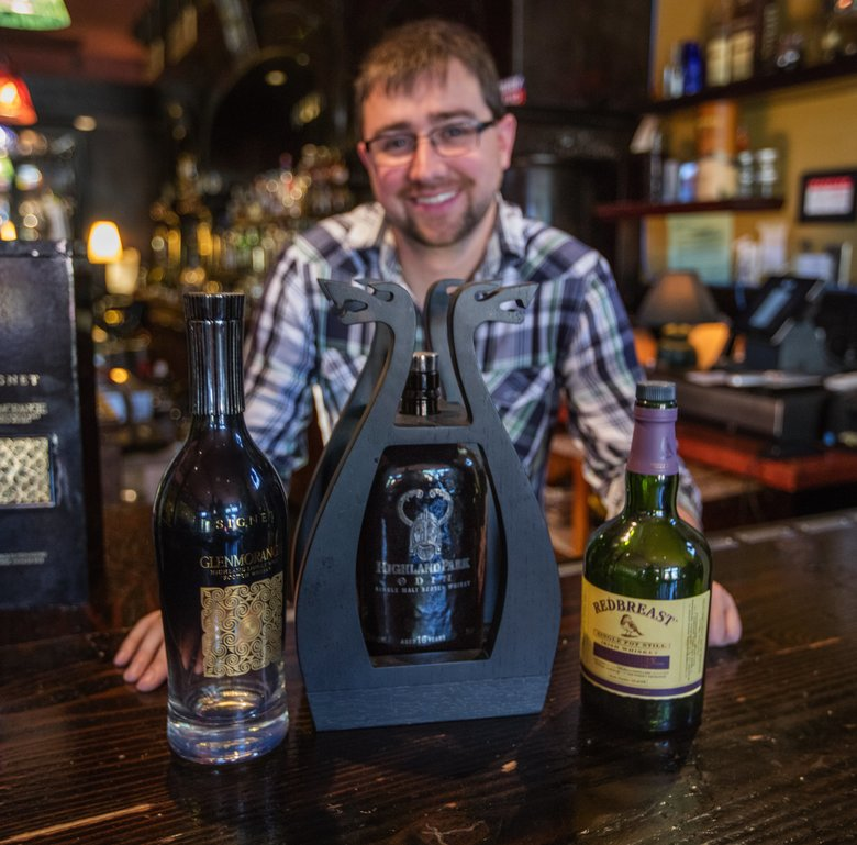 Travis Sanders, manager of Mulleady's, with bottles of Glenmorangie Signet, left, Highland Park Odin and Redbreast all Sherry Cask. Many bars offer so-called break-even bottles occasionally but this Magnolia pub always does.  (Steve Ringman/The Seattle Times)