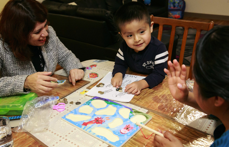 "Perla Campbell, with the Parent-Child Home Program, from left, works with David e Manuel Flores, 3, and his mother Patricia Agudo at their home in Seattle's Beacon Hill neighborhood Wednesday, Nov. 16, 2016. ""He's so smart,"" says Campbell. Campbell brought a puzzle to their home, and practiced counting and identifying colors with David and his mother."
