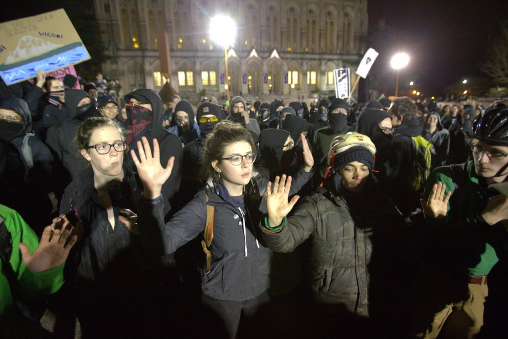 A group of students tries to create a protective buffer between groups in Red Square. Controversial Breitbart News editor Milo Yiannopoulos was to speak at Kane Hall on the University of Washington campus Friday. (Dean Rutz / The Seattle Times)