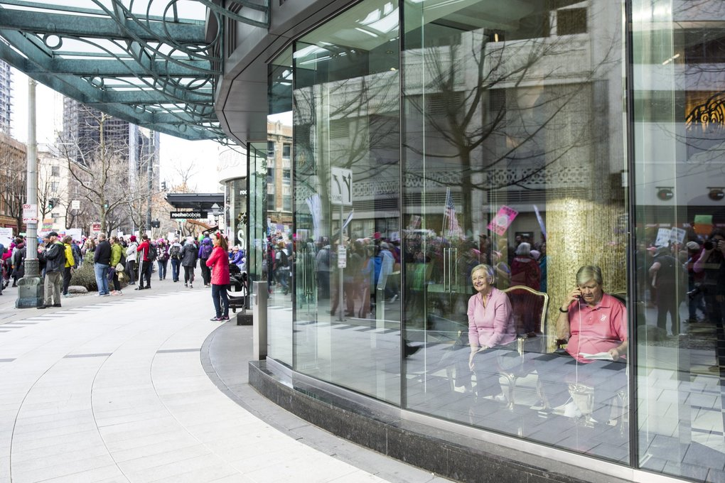 A couple watches from inside the Escala building as the Womxn's March on Seattle.   (Bettina Hansen / The Seattle Times)