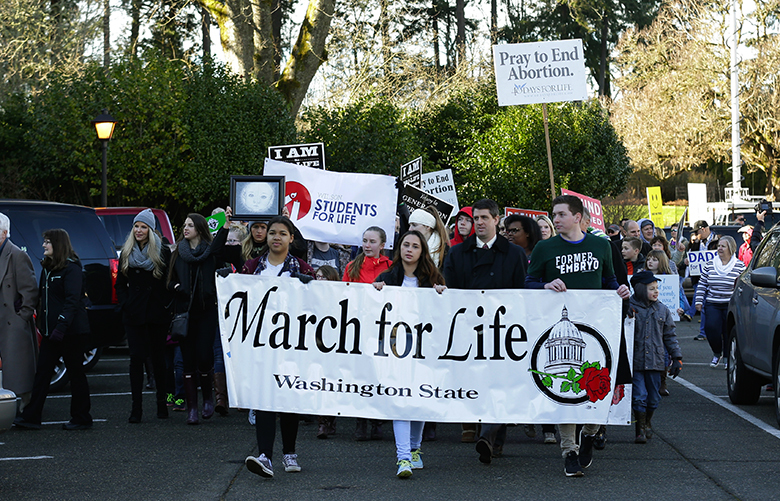 Participants in an anti-abortion rally and march carry signs and banners as they arrive at the Capitol in Olympia, Wash., Monday, Jan. 23, 2017. (AP Photo/Ted S. Warren)