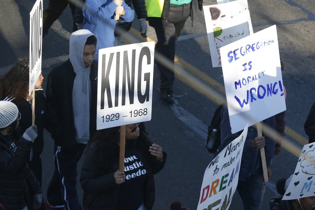 Signs carried by the marchers honor the Rev. Martin Luther King Jr., the civil-rights leader who is remembered with a federal holiday on the third Monday in January. King, whose actual birth date was Jan. 15, 1929, was 39 when he was assassinated in 1968.  (Logan Riely/The Seattle Times)