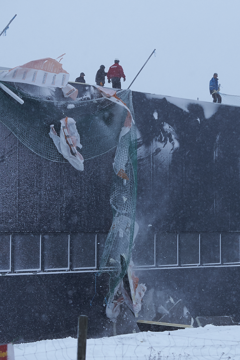 Workers secure insulating boards on the roof of a hall that is still under construction in the industrial park in Simmern, Germany, Friday, Jan. 13, 2017.  Heavy snowfalls and strong winds caused damages in parts of Germany. (Thomas Frey/dpa via AP)
