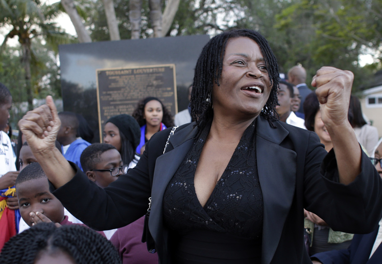 "Marleine Bastien, executive director of Haitian Women of Miami (FAMN), reacts after hearing the news that President Barack Obama repealed a longstanding immigration policy known as ""wet foot, dry foot"" which allows any Cuban who makes to U.S. soil to stay and become a legal resident, Thursday, Jan. 12, 2017, in Miami. Bastien was attending vigil to commemorate the seventh anniversary of the earthquake that devastated Haiti in 2010. (AP Photo/Lynne Sladky)"