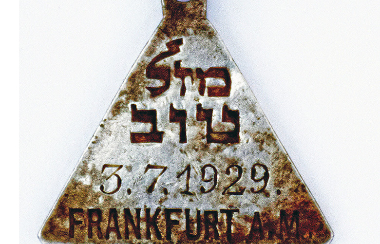 """This undated photograph released by the Israel Antiquities Authority shows a pendant that appears identical to one belonging to Anne Frank, Israel's Yad Vashem Holocaust memorial said Sunday. Yad Vashem says it has ascertained the pendant belonged to Karoline Cohn _ a Jewish girl who perished at Sobibor and may have been connected to the famous diarist. Both were born in Frankfurt in 1929 and historians have found no other pendants like theirs. The triangular piece found has the words """"Mazal Tov"""" written in Hebrew on one side along with Cohn's date of birth and the Hebrew letter """"heh,"""" an initial for God, as well as three Stars of David on the other. (Yoram Haimi, Israel Antiquities Authority via AP) DV501 DV501"""