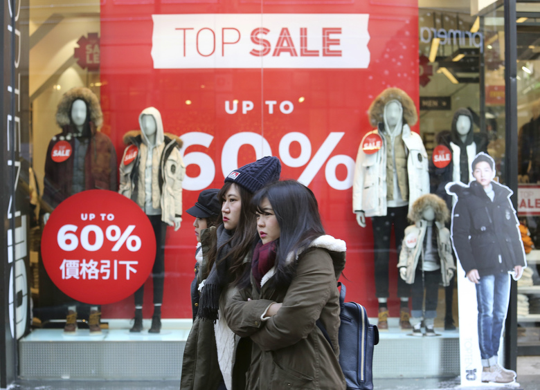 Women pass by sale signs at a shopping district in Seoul, South Korea, Friday, Jan. 13, 2017. South Korea's central bank lowered its forecast for the country's growth in 2017 due partly to the fallout from a massive influence-peddling scandal. (AP Photo/Ahn Young-joon)