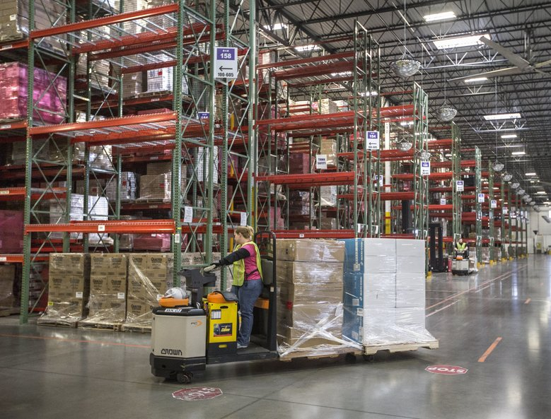 A worker moves products at the Amazon Fulfillment Center in DuPont. Many of the new jobs that Amazon will create in the next 18 months will be at fulfillment centers currently being built. (Steve Ringman/The Seattle Times)