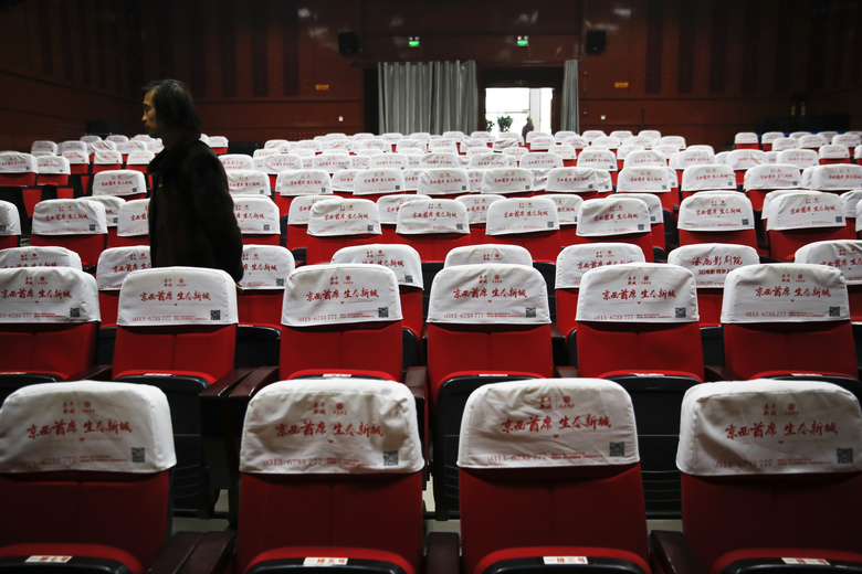 In this Dec. 12, 2016 photo, Wang Xudong, the manager of Zhuolu County Digital Cinema, checks on the main screening hall in Zhuolu county in north China's Hebei province. The brightly-decorated 3-D cinema in this town outside Beijing is showing the latest Chinese and Hollywood films, to row after row of empty red seats. So few people come to watch films here that the theater manager rents out the halls to travelling sales companies or music teachers. (AP Photo/Andy Wong)